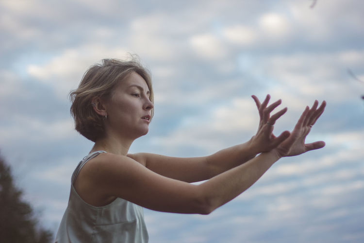 Portrait of woman with arms raised against sky