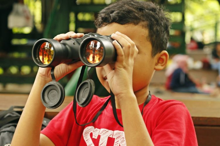 Close-up of boy looking through binoculars
