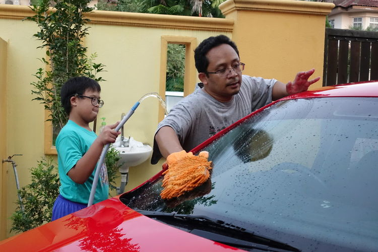 Boy Assisting Father While Washing Car