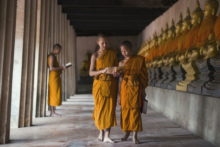 Monks Reading Book While Walking In Corridor