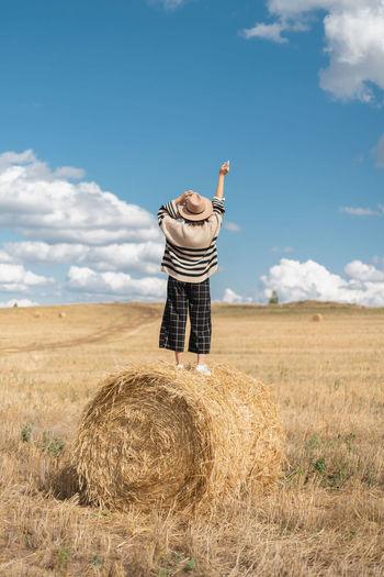 Man standing by hay bales on field against sky