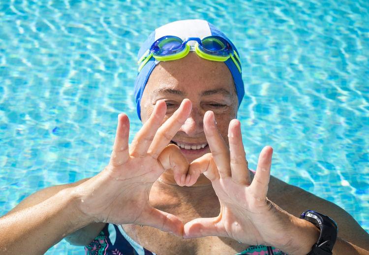 Portrait of shirtless man swimming in pool