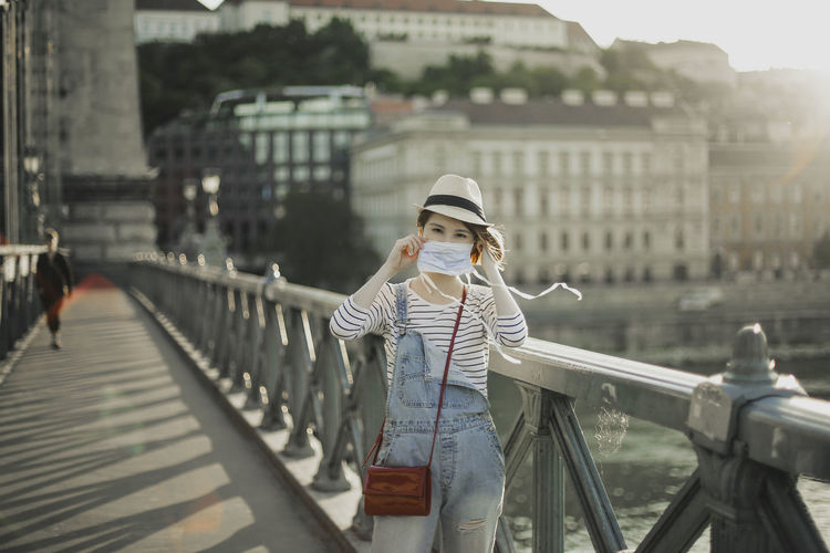 Portrait of young woman wearing face mask on bridge in city