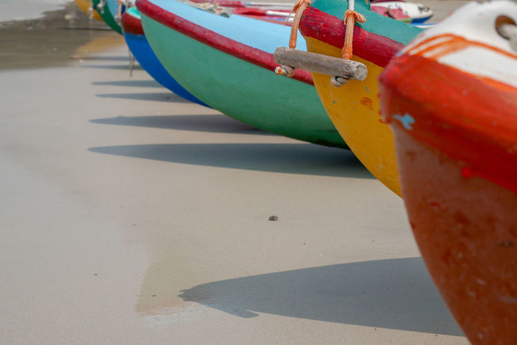 Close-up of red boats moored on beach