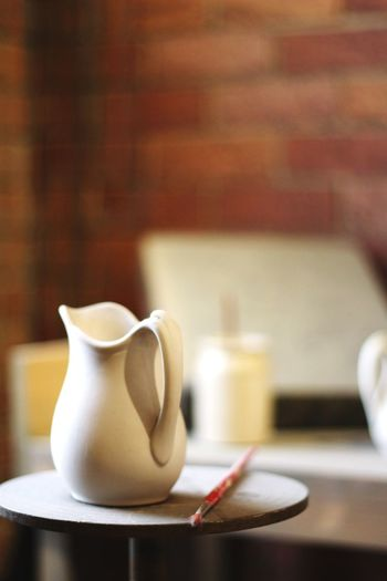 Close-Up Of Jug And Brush On Table