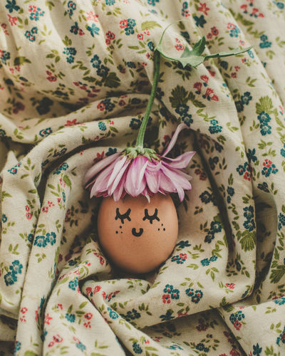 High angle view of painted egg on floral pattern fabric