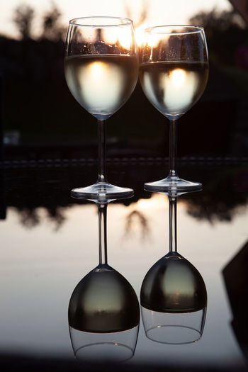 Romantic couple of glasses of wine on a table with reflections and sunset in the background Celebration Couple Wedding Win An EyeEm T-Shirt Alcohol Close-up Couple - Relationship Day Drink Evening Focus On Foreground Food And Drink Freshness Glass Glass - Material Party Reflection Refreshment Still Life Sunset Table Transparent White Wine Wineglass