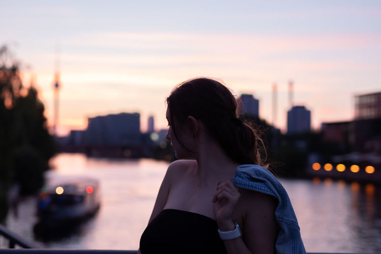 Thoughtful woman standing against river during sunset