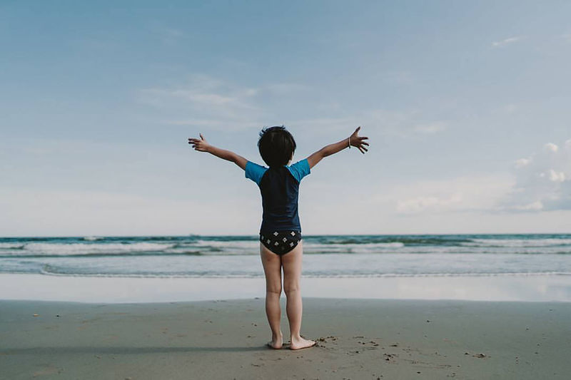 Full length rear view of boy standing at beach