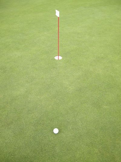High Angle View Of Golf Ball With Flag On Grass
