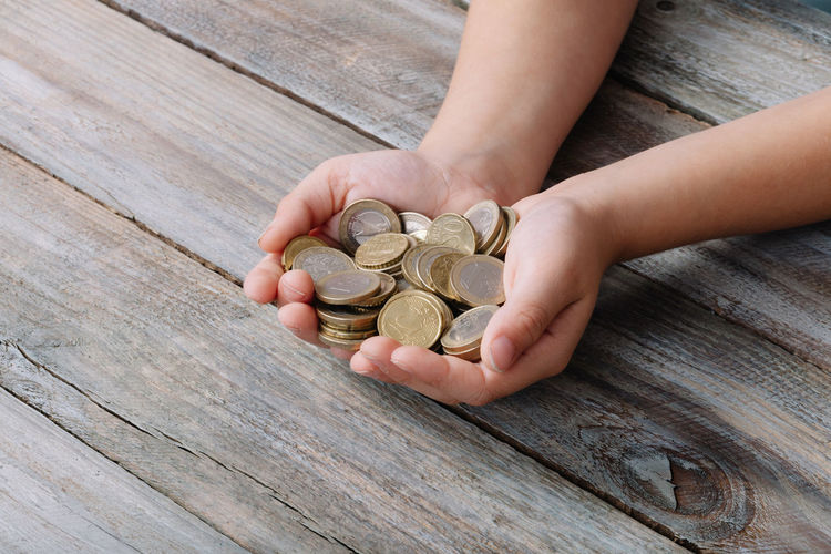 Cropped hands of boy holding coins on wooden table
