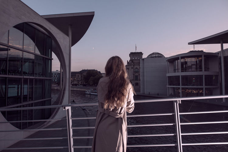 Rear view of woman leaning on railing against sky