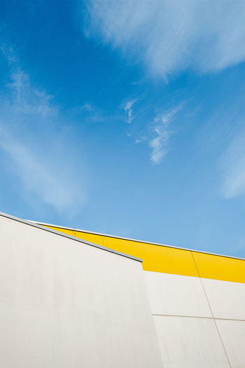 Low angle view of yellow building against blue sky
