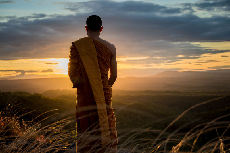 Rear view of monk standing on field against sky at sunset