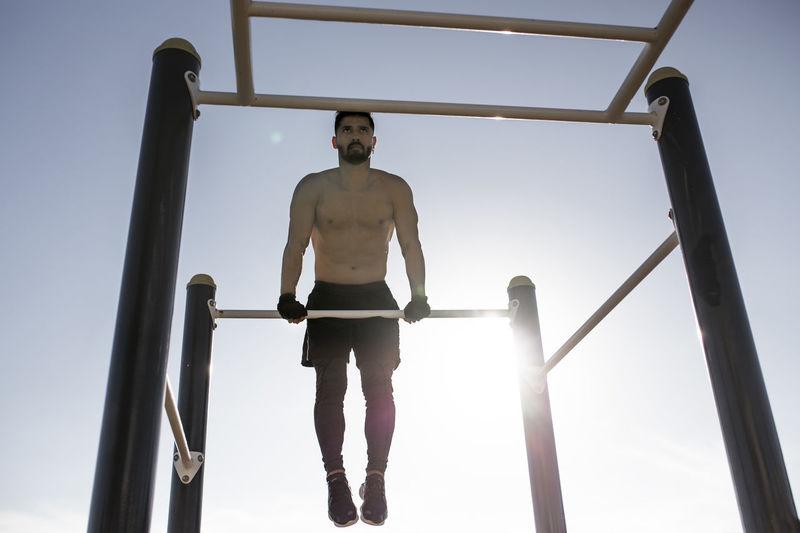Full length of shirtless man standing against sky