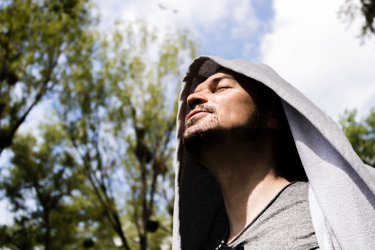 Low angle view of man with eyes closed in park