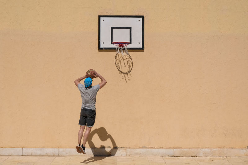 One Person Basketball - Sport Full Length Wall - Building Feature Basketball Hoop Real People Lifestyles Leisure Activity Sport Architecture Court Basketball - Ball Casual Clothing Motion Ball Built Structure Men Standing Day Arms Raised Human Arm Effort Skill  Competitive Sport Jumping 17.62°