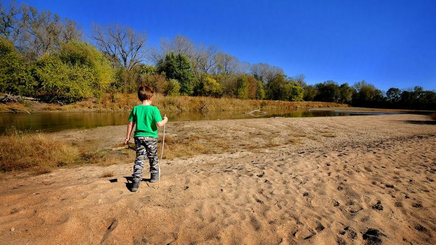 Rear View Of Boy Walking On Sand At Little Blue River