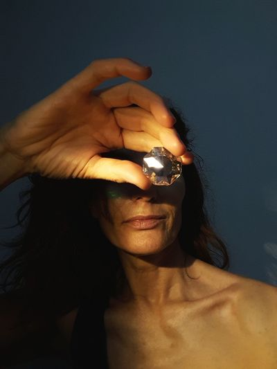 Close-up of woman holding diamond in front of face
