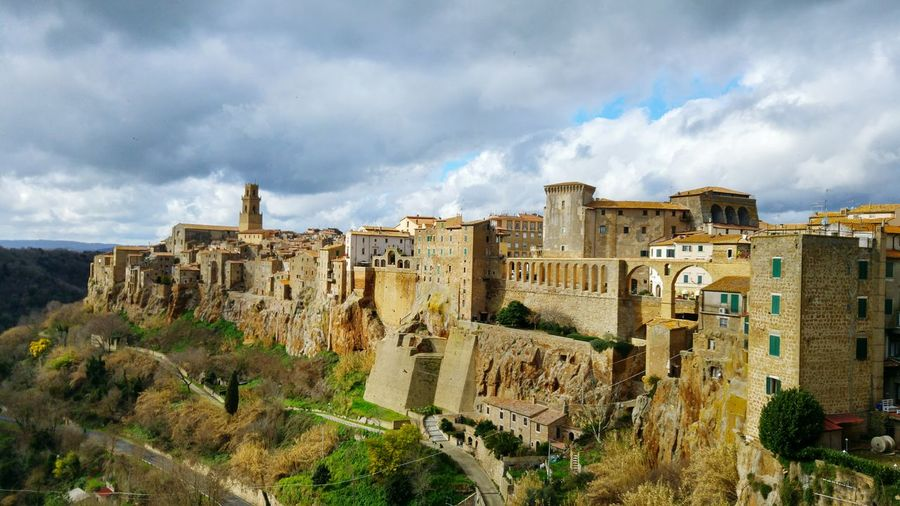 Historic buildings in pitigliano against cloudy sky