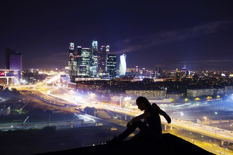 Silhouette woman sitting on terrace against illuminated cityscape at night