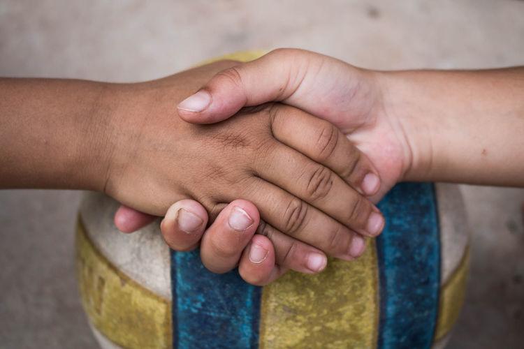 Close-Up Of Children Doing Handshake Over Ball