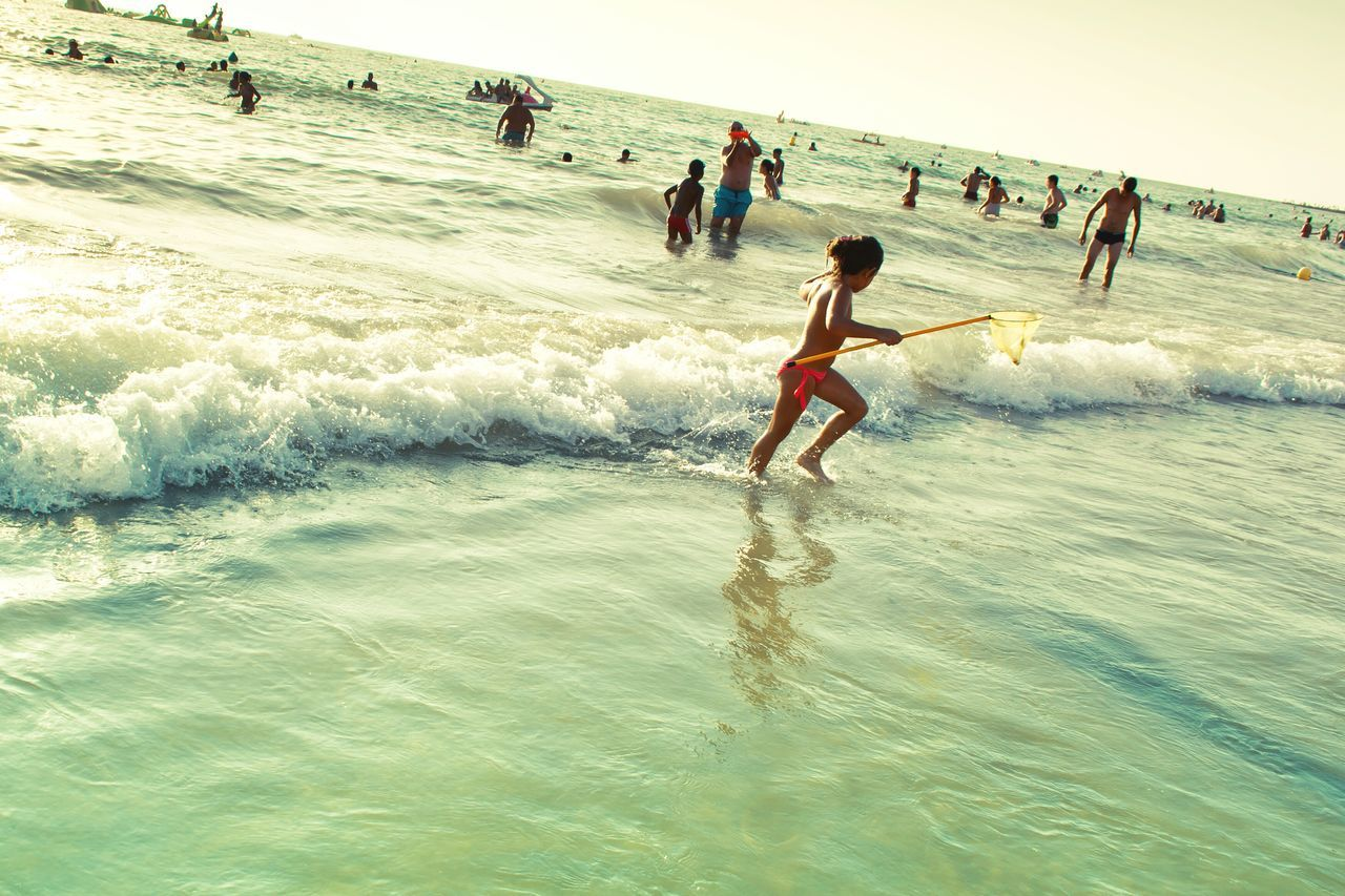 real people, beach, leisure activity, nature, motion, sand, enjoyment, fun, lifestyles, water, vacations, sea, beauty in nature, men, playing, large group of people, wave, outdoors, day, scenics, full length, sky, people