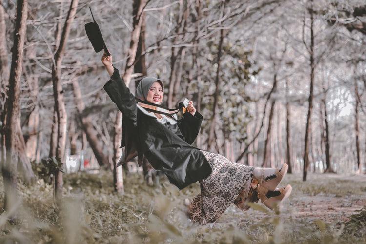 Full length of woman holding hat levitating against trees