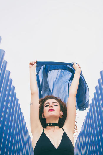 Portrait Of Young Woman Holding Blue Scarf Amidst Corrugated Irons Against Clear Sky
