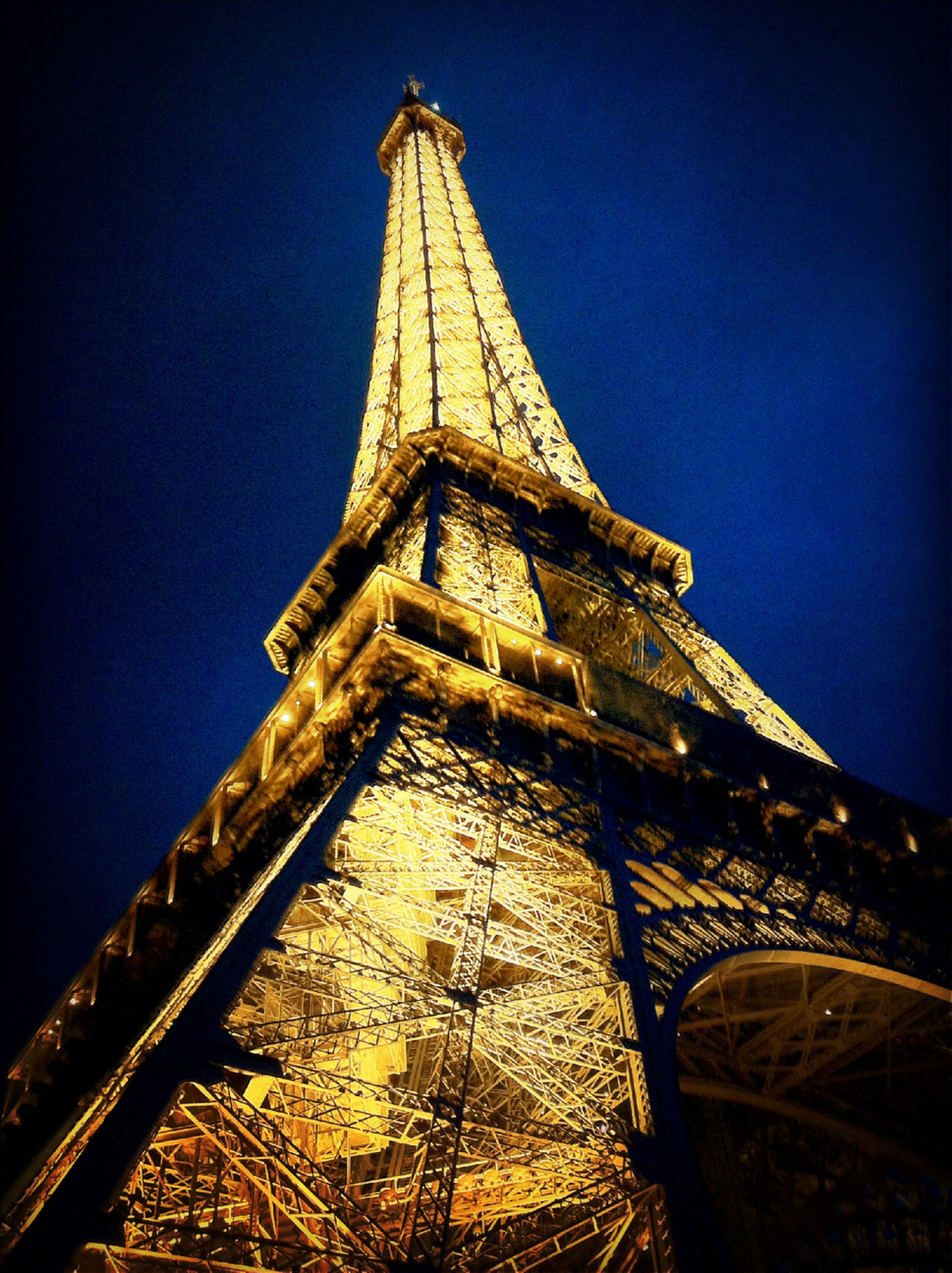 low angle view, architecture, built structure, tower, clear sky, famous place, building exterior, blue, travel destinations, tall - high, international landmark, eiffel tower, travel, tourism, capital cities, sky, culture, illuminated, night, clock tower