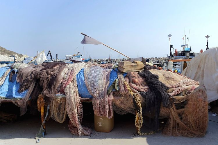Fishing nets at harbor against clear sky