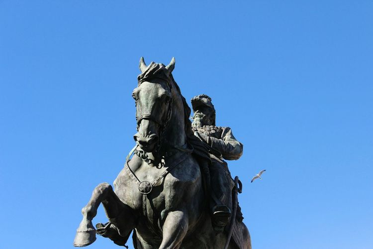 Low angle view of man and horse statute against clear blue sky