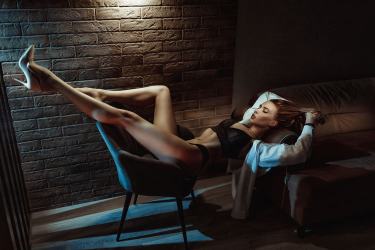 Full length of woman lying on wall at home