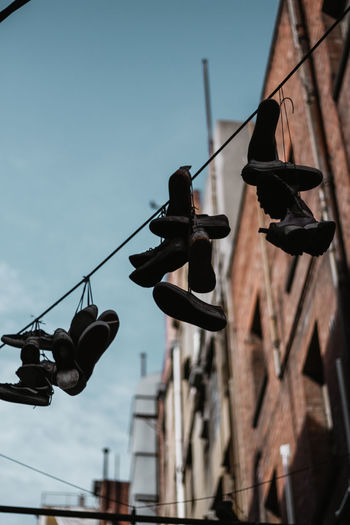 Low angle view of shoes hanging on street against sky