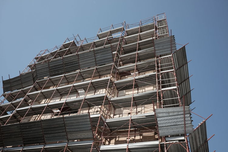 scaffolding with protection on the building Façade Industrial Renovation Scaffolding Building Building Exterior Construction Industry Construction Site Incomplete Metallic No People Outdoors Protective Reconstruction Safety Scaffold Structure