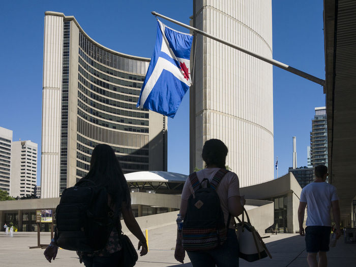 Silhouette of a couple walking in front of Toronto city hall building. American Flag Architecture Building Exterior Built Structure City City Life Clear Sky Development Flag Flying Identity Leisure Activity Lifestyles Men Modern Office Building Outdoors Patriotism Person Pride Skyscraper Tall - High Toronto Flag Tower Urban Skyline