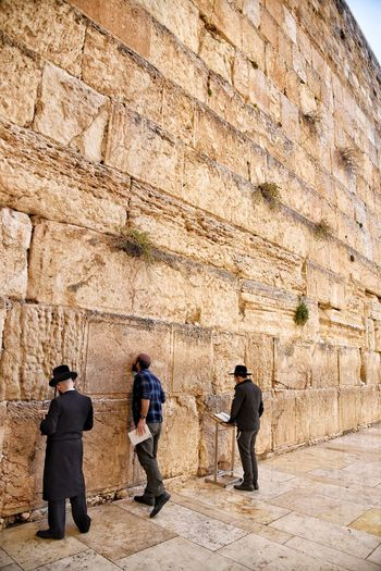 Rear view of people standing against wall