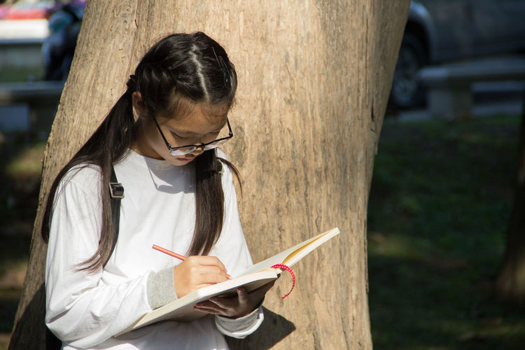 Book Casual Clothing Childhood Concentration Day Education Eyeglasses  Girls Grass Holding Intelligence Learning Leisure Activity Lifestyles Note Pad One Person Outdoors Pen Pencil Real People Sitting Sketch Pad Student Tree Writing