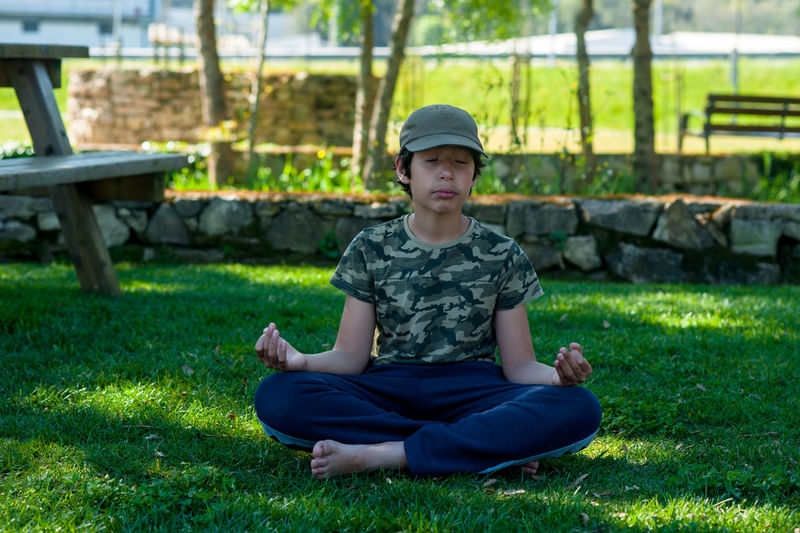 Boy meditating at park