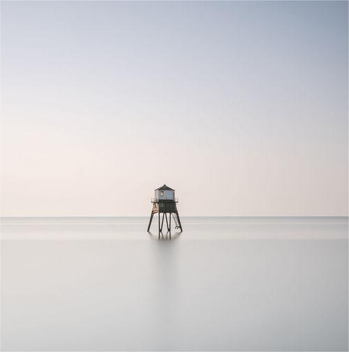 Lifeguard hut amidst sea against clear sky