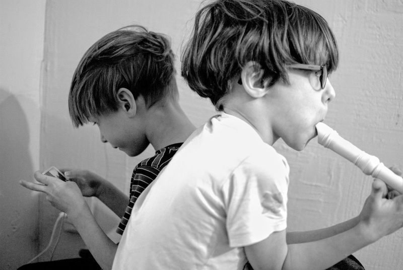 Two People Child Childhood Togetherness Elementary Age Boys Children Only Indoors  Friendship People Headshot Close-up Day Black And White Brothers Playing Flute Playing Music Playing With Apps  Sitting