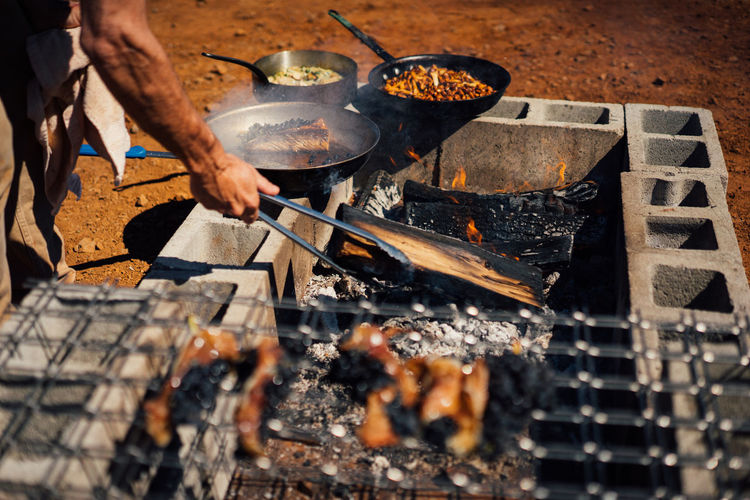High angle view of man preparing meat on barbecue grill