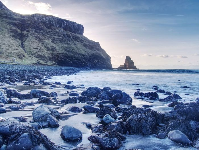 Talisker bay on the isle of skye in scotland. foamy sea, boulders and large cracked rocks in ocean