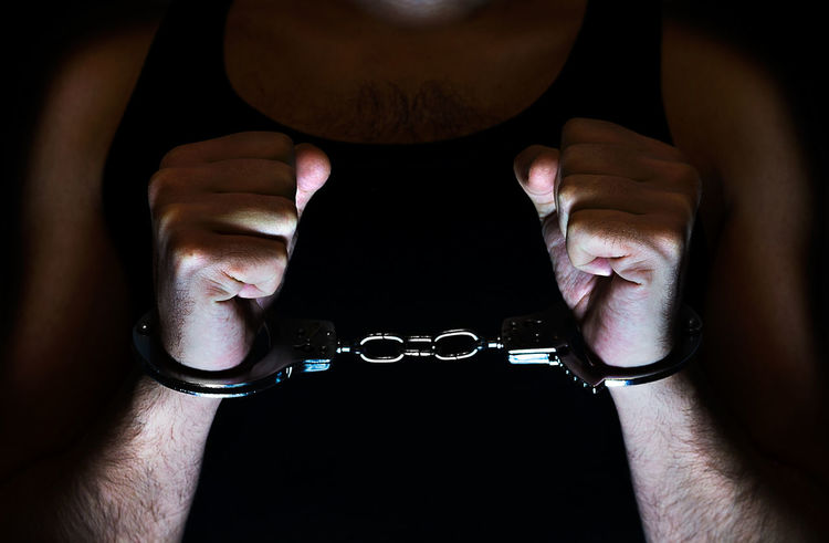 Man hands with handcuffs in dramatic light Crime Arrest Black Background Adult People Man Men Young Adult Fists Handcuffed Illegal Arrested Dramatic Light Cuffs Tied Hands Kidnapped Burglar Thief Caught Penitentiary Jailed One Person Human Body Part
