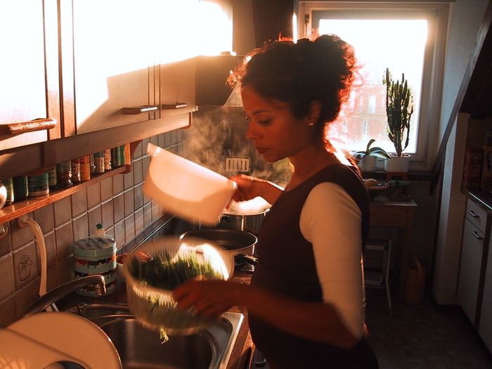 Young pregnant woman washing vegetables in kitchen