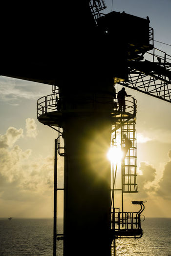 Oil and gas industries. Silhouette of pedestal crane operator working on oil and gas platform in the middle of the sea descending using monkey ladder after working hours. Commissioning Construction Industrial Production RISK Transportation Commercial Compensation Drilling Engineering Exploration Hazard Installation Job Mega Structure Occupation Occupational Safety And Health Offshore Platform Oil And Gas Platform Progress Rig Safety Source Technology
