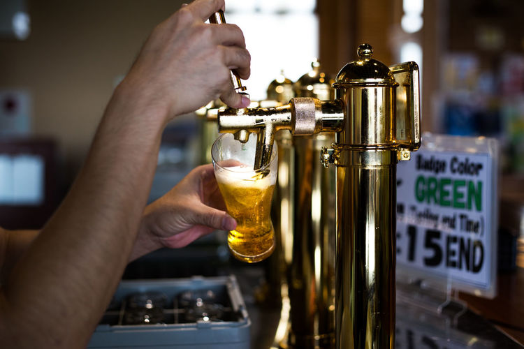 Close-Up Of Hand Serving Beer