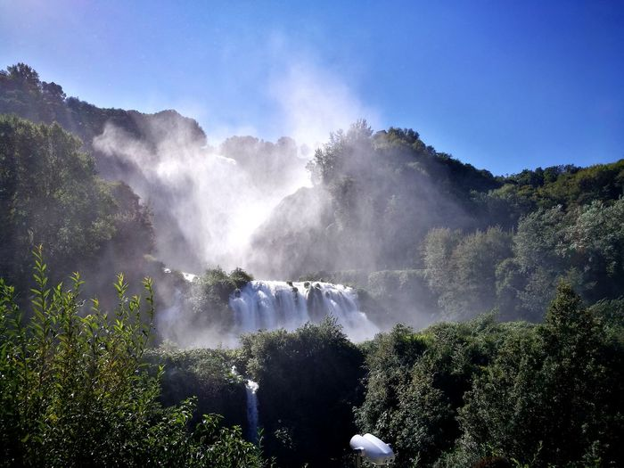 Panoramic view of waterfall in forest against sky