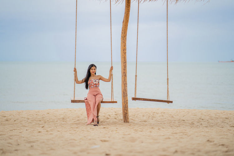 Full length of woman on swing at beach against sky