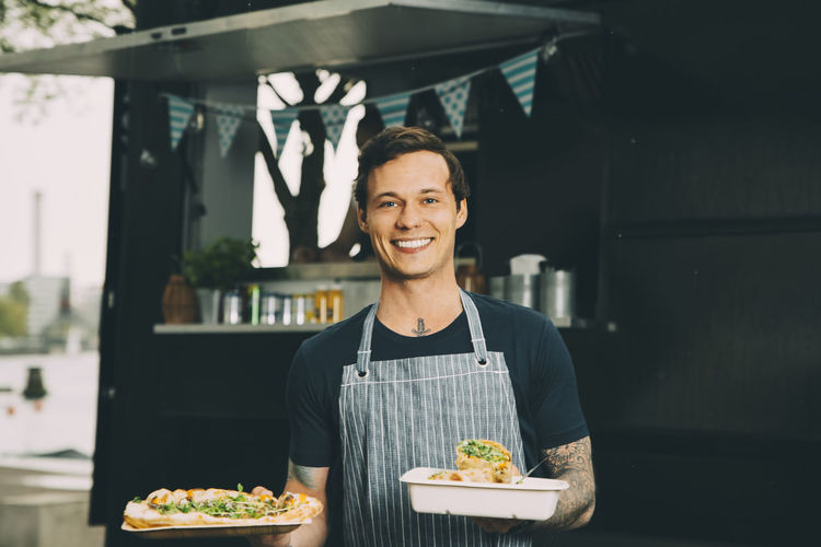 Portrait of a smiling young man holding food